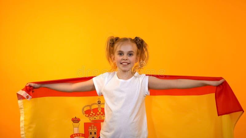 Muchacha española adorable que salta con la bandera que anima para el equipo de fútbol preferido, fan imágenes de archivo libres de regalías
