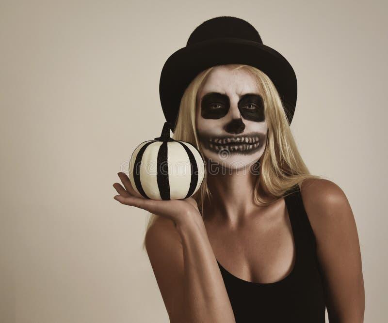 Muchacha esquelética asustadiza de Halloween que sostiene la decoración de la calabaza imagenes de archivo