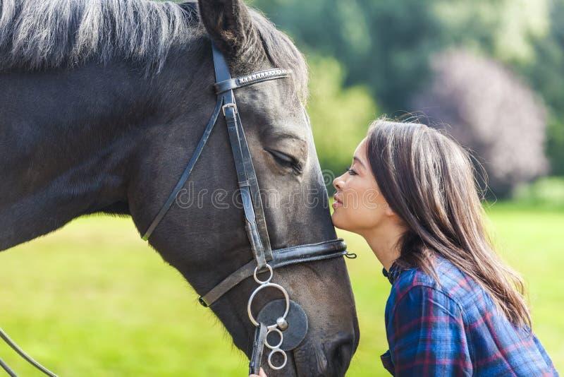 Muchacha eurasiática asiática hermosa con su caballo fotos de archivo
