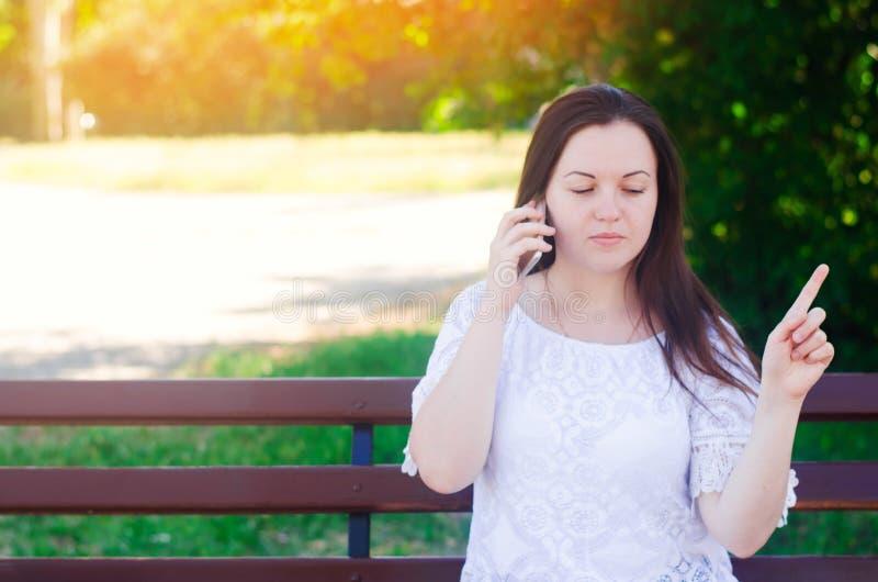 Muchacha europea hermosa joven que se sienta en un banco y que habla en el teléfono La muchacha señala un finger lejos, da consej foto de archivo