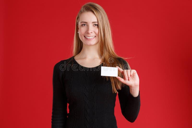 Muchacha europea sonriente, sosteniendo una tarjeta de visita vacía en una mano imagen de archivo