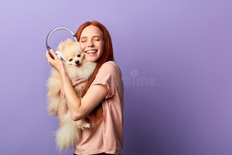 Muchacha extática que abraza su animal doméstico adorable imagenes de archivo
