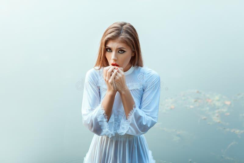 Muchacha extraña en un vestido blanco imagen de archivo