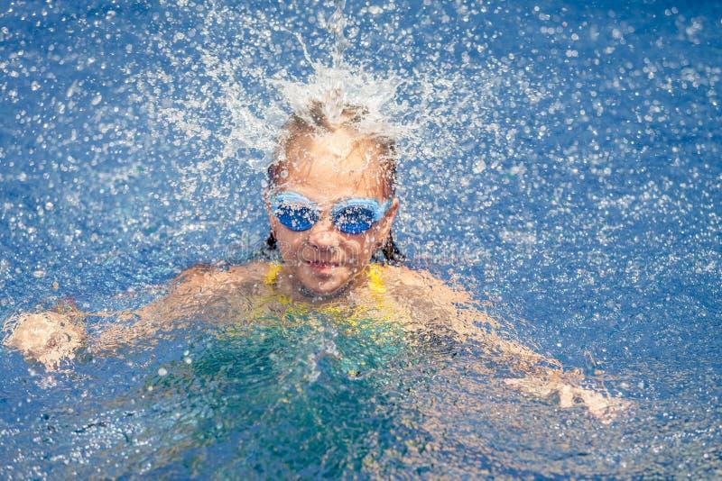 Muchacha feliz adolescente que juega en la piscina foto de archivo libre de regalías