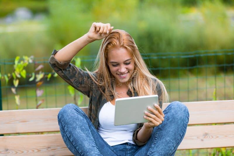 Muchacha feliz al aire libre con una tableta imágenes de archivo libres de regalías
