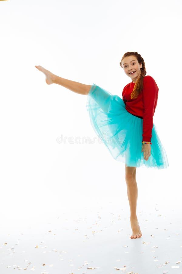 Muchacha feliz alegre que detiene su pierna fotos de archivo