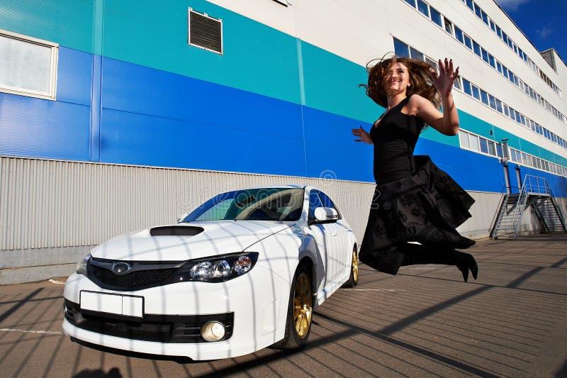 Muchacha feliz alegre que salta cerca del coche blanco foto de archivo libre de regalías