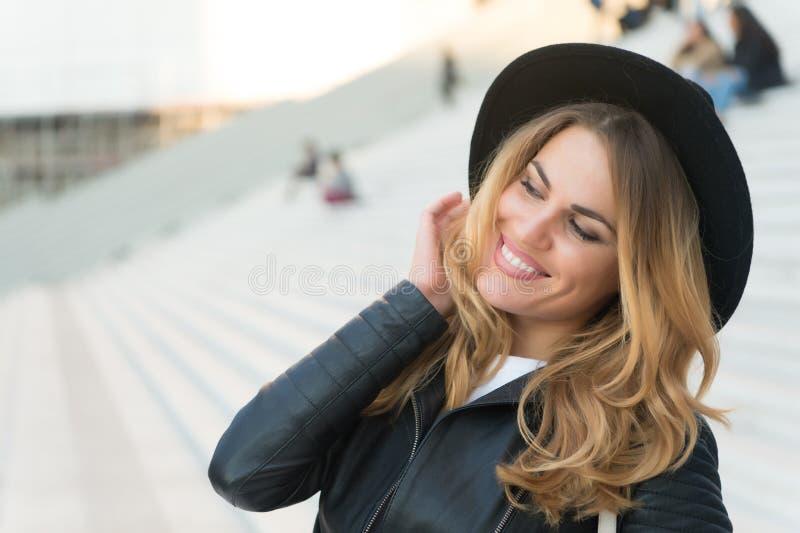 Muchacha feliz con el pelo rubio largo, peinado, en París, Francia Muchacha en la sonrisa al aire libre, moda del sombrero negro  imagen de archivo