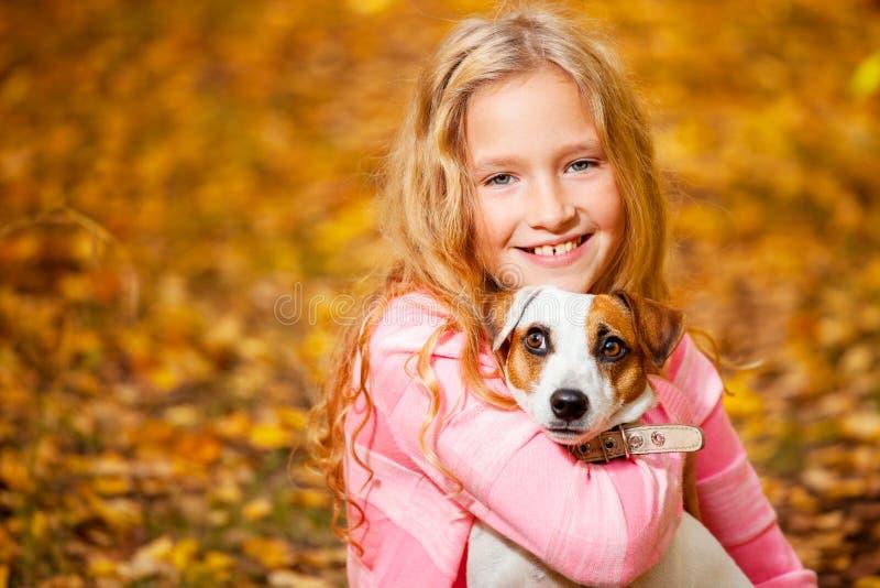 Muchacha feliz con el perro en el otoño imagen de archivo libre de regalías