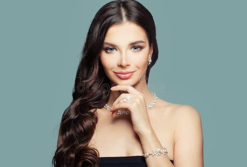 Muchacha feliz con joyería Mujer morena con maquillaje y el peinado rizado y collar de diamantes en fondo azul imagen de archivo libre de regalías