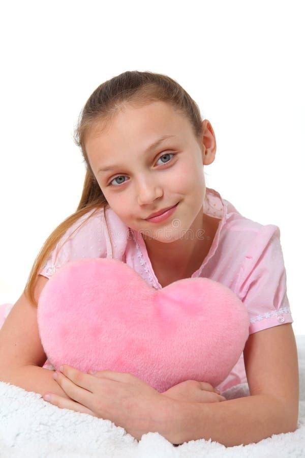 Muchacha feliz con la almohada rosada del corazón fotos de archivo