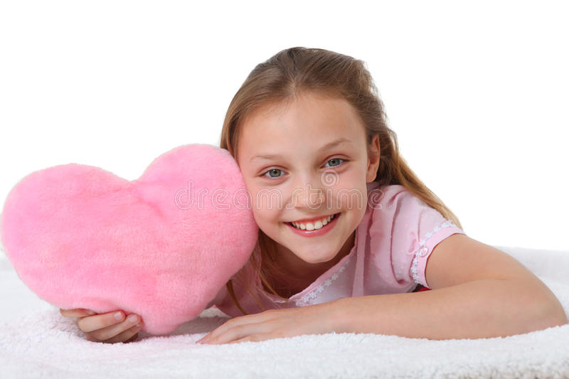 Muchacha feliz con la almohada rosada del corazón fotos de archivo libres de regalías