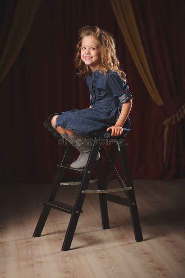 Muchacha feliz con la cortina del teatro en fondo imagen de archivo