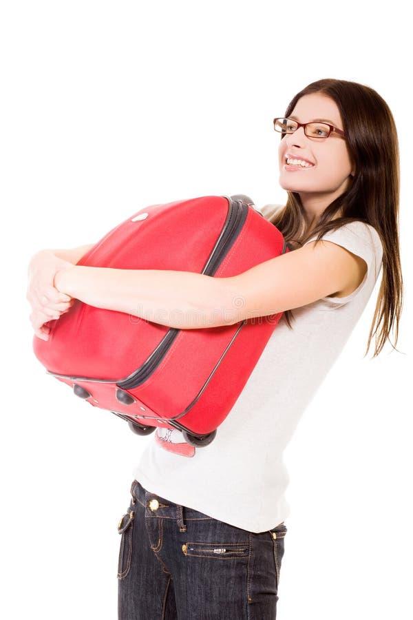 Muchacha feliz con la maleta en un fondo blanco imagenes de archivo