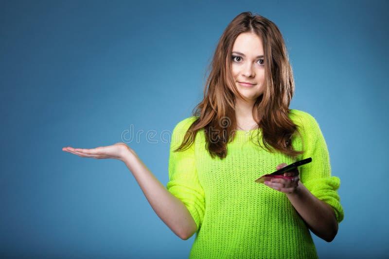 Muchacha feliz con la palma abierta del teléfono móvil para el producto fotos de archivo libres de regalías