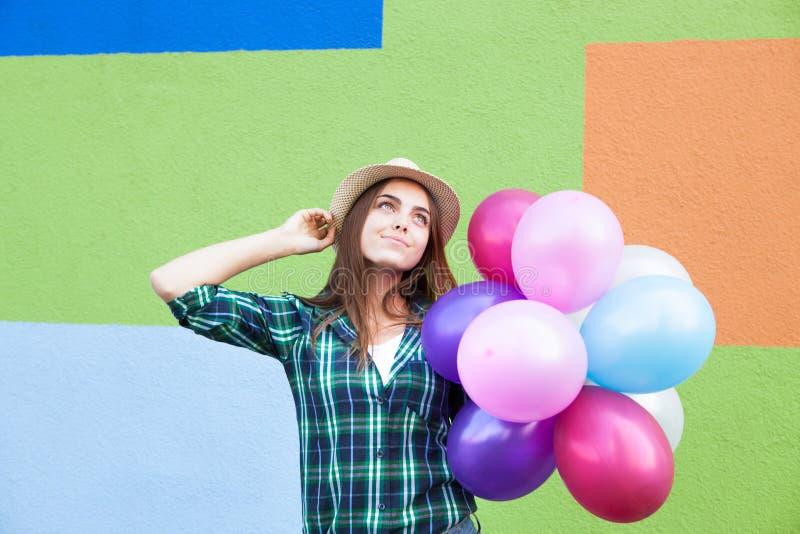 Muchacha feliz con las pecas con los globos que miran para arriba, cerca de la pared colorida en verano foto de archivo