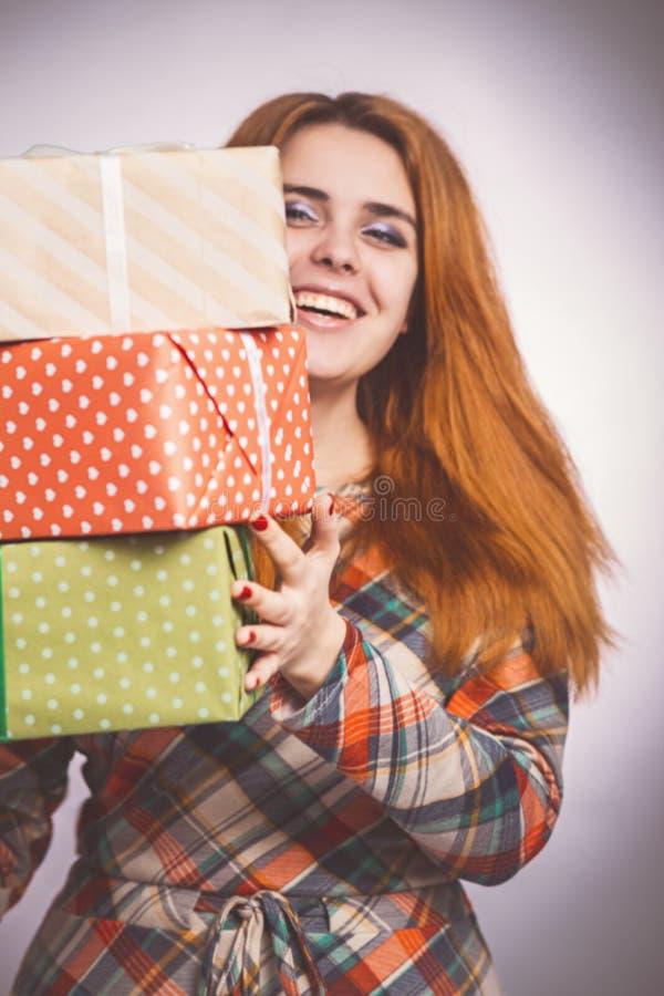 Muchacha feliz con las porciones de regalos en manos, de una mujer joven que sostiene una pila de cajas envueltas en papel decora foto de archivo libre de regalías