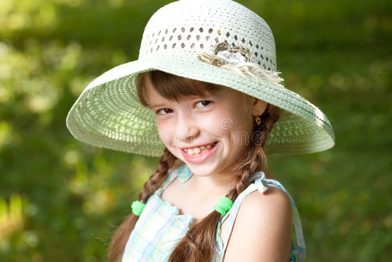 Muchacha feliz con las trenzas en el sombrero imagenes de archivo