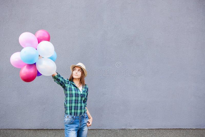 Muchacha feliz con los globos cerca de la pared gris con el espacio de la copia imagenes de archivo