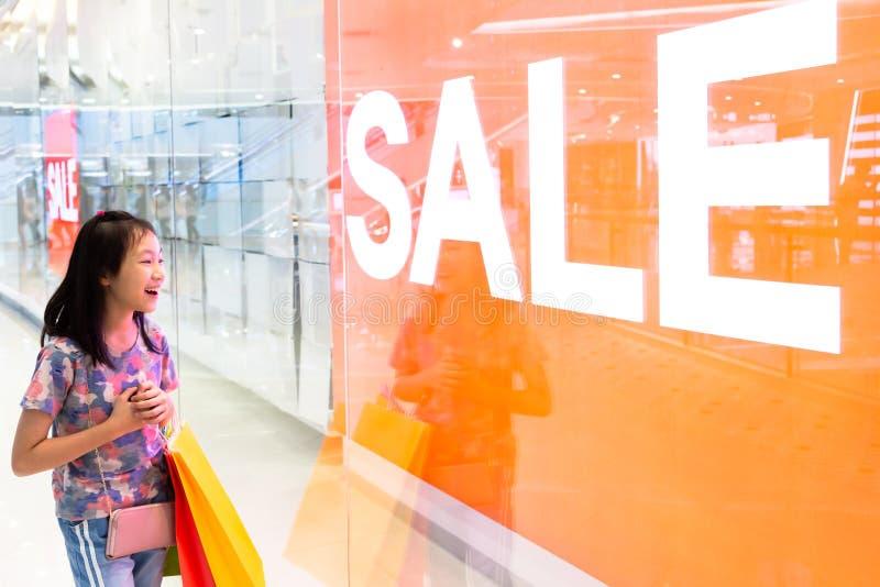Muchacha feliz con los panieres que miran para hacer compras ventana en alameda fotografía de archivo libre de regalías