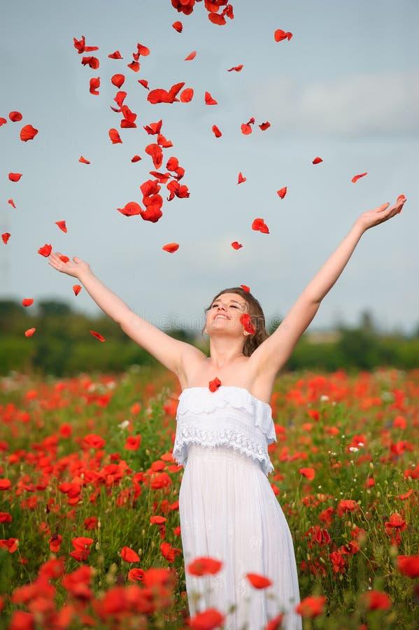 Muchacha feliz con para arriba aumentados los brazos en el campo verde de flores Concep imagen de archivo