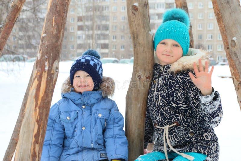 Muchacha feliz con sonrisa del pequeño hermano durante las nevadas fotografía de archivo