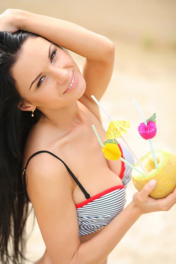 Muchacha feliz con un coctel en la playa fotografía de archivo libre de regalías