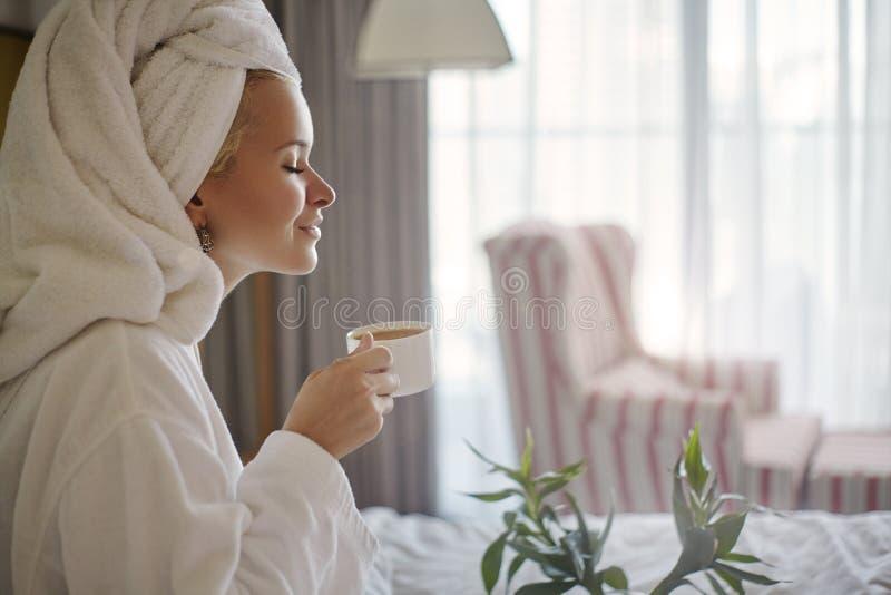 Muchacha feliz con una taza de caf? Albornoz que lleva y toalla del estilo de la mujer casera de la relajaci?n despu?s de la duch imagen de archivo