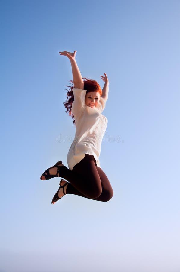 Muchacha feliz de la diversión, y un salto de la libertad imagenes de archivo