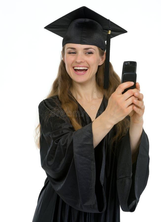 Muchacha feliz de la graduación que hace la foto del uno mismo por el teléfono fotos de archivo libres de regalías