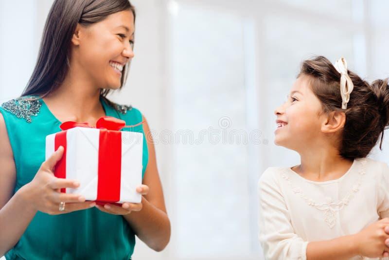 Muchacha feliz de la madre y del niño con la caja de regalo foto de archivo libre de regalías