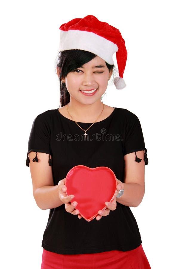 Muchacha feliz de Navidad que sostiene la caja en forma de corazón fotos de archivo