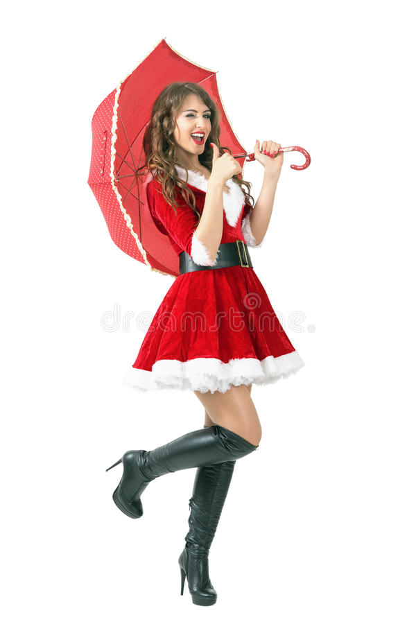 Muchacha feliz de Papá Noel con el paraguas que guiña en la cámara con los pulgares para arriba foto de archivo libre de regalías