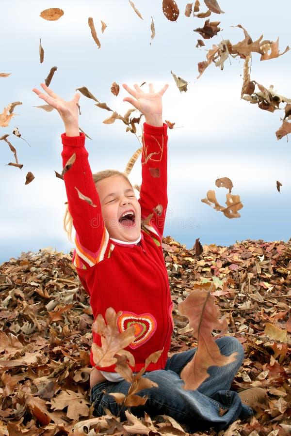 Muchacha feliz de siete años que juega en la pila de hojas fotografía de archivo