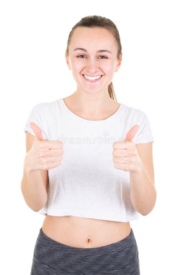 Muchacha feliz del ajustado en la demostración de la ropa de deportes su vientre y pulgar planos para arriba aislados en el fondo fotos de archivo libres de regalías
