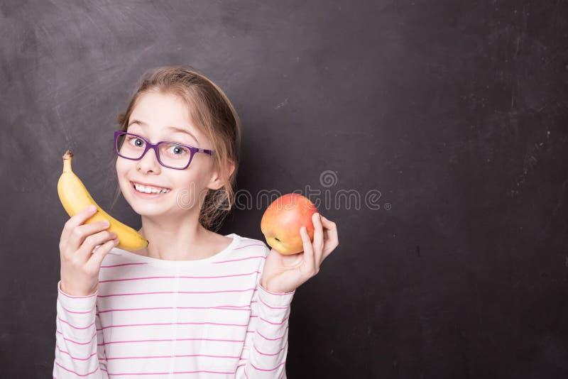 Muchacha feliz del chid con la manzana y el plátano en la pizarra fotografía de archivo libre de regalías