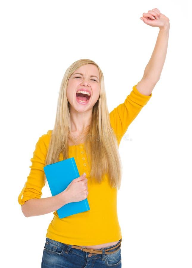 Muchacha feliz del estudiante con éxito del júbilo del libro foto de archivo