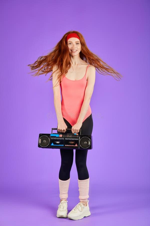 Muchacha feliz del estudiante con danza roja rizada larga del pelo con el reproductor de casete retro portátil imagenes de archivo