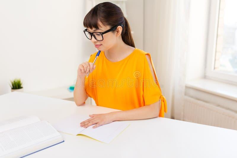 Muchacha feliz del estudiante con el libro y el cuaderno en casa fotografía de archivo