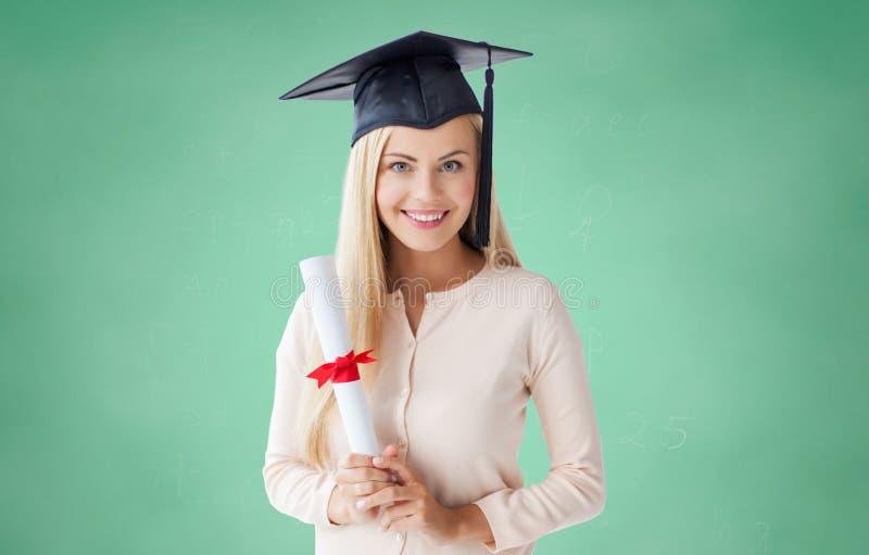 Muchacha feliz del estudiante en casquillo del soltero con el diploma imagenes de archivo
