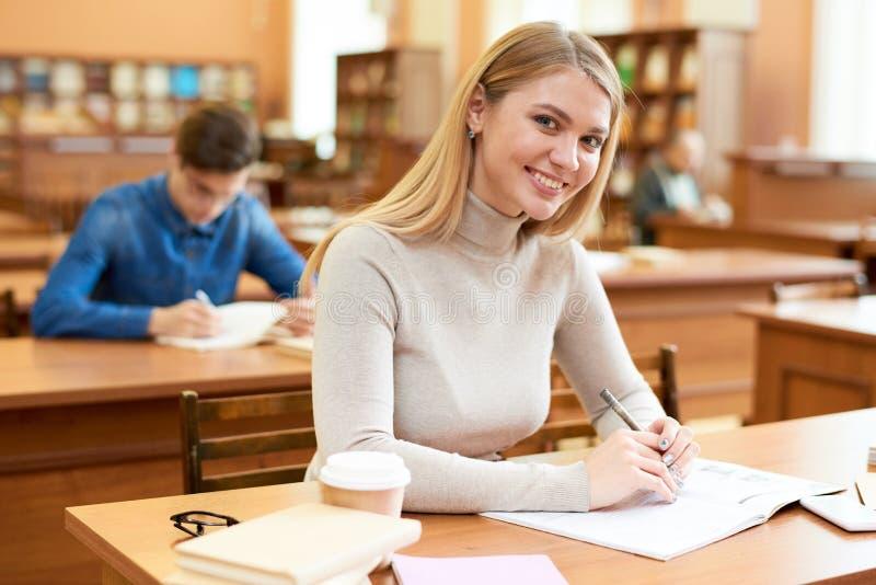 Muchacha feliz del estudiante que disfruta de tiempo en biblioteca fotos de archivo