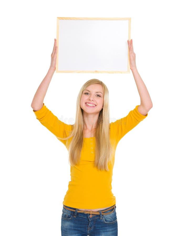 Muchacha feliz del estudiante que lleva a cabo a la tarjeta en blanco de arriba imagen de archivo libre de regalías