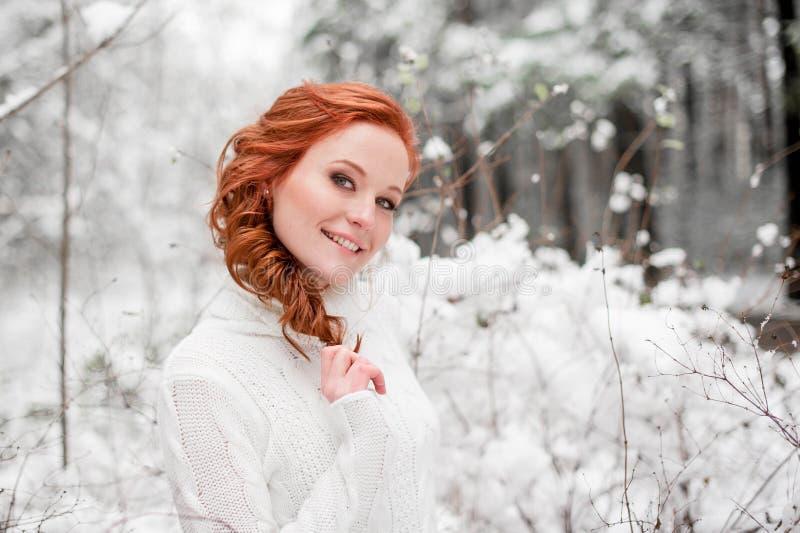 Muchacha feliz del jengibre en el suéter blanco en la nieve diciembre del bosque del invierno en parque Retrato Tiempo lindo de l foto de archivo