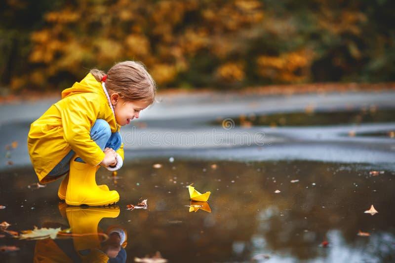 Muchacha feliz del niño con el barco de papel en charco en otoño en natu imagenes de archivo