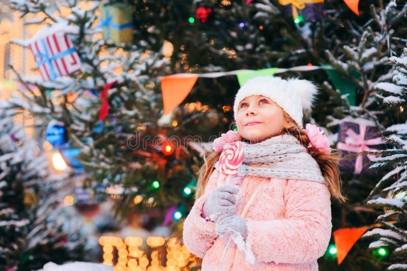 muchacha feliz del niño con el caramelo de la Navidad Retrato de las vacaciones de invierno en el árbol de navidad foto de archivo