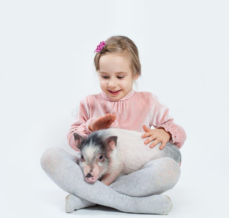 Muchacha feliz del niño con el cerdo Niño y animal doméstico imagenes de archivo
