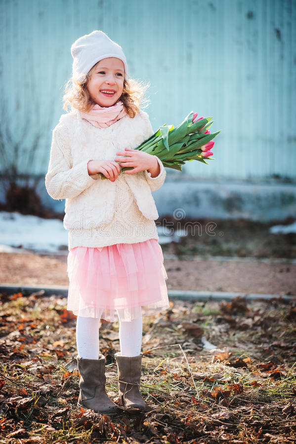 Muchacha feliz del niño con el ramo de los tulipanes para el día de la mujer en el paseo en primavera temprana fotografía de archivo libre de regalías