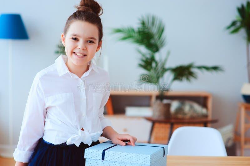 Muchacha feliz del niño con el regalo para el cumpleaños o el día de la mujer que presenta en casa imagenes de archivo