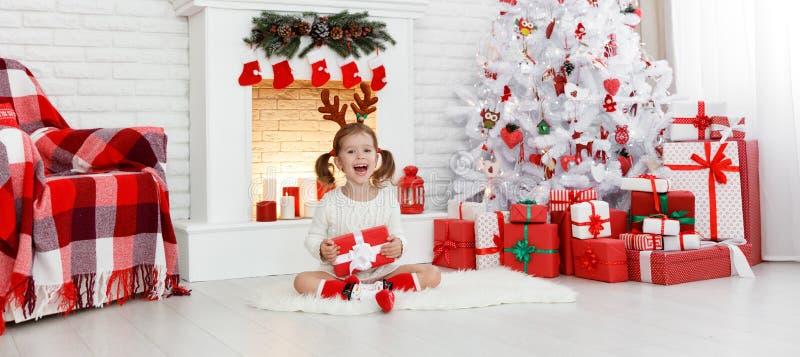 Muchacha feliz del niño con el regalo por mañana en el árbol de navidad imagen de archivo