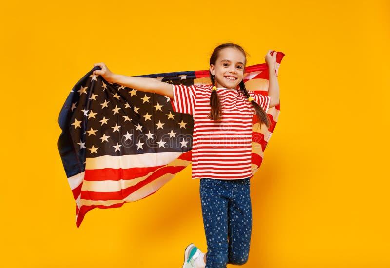 Muchacha feliz del niño con la bandera de los Estados Unidos de América los E.E.U.U. en fondo amarillo foto de archivo